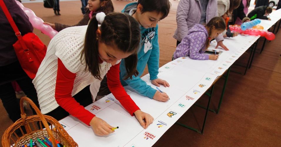 11.dez.2012 - Crianças escrevem seus pedidos na tentativa de bater o recorde da maior carta de Natal do mundo eviada ao Papai Noel, em Pantelimon, cidade próxima a Bucareste, na Romênia. A carta mede 1.500 metros