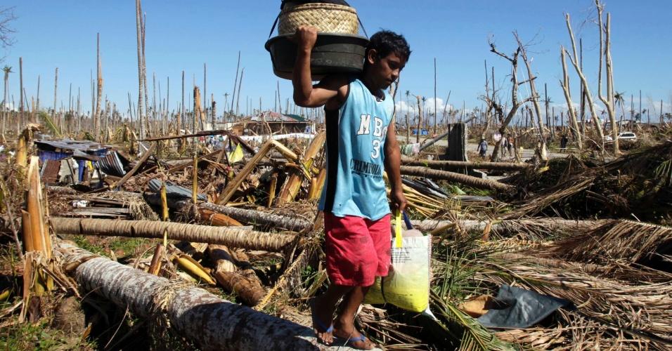 11.dez.2012 - Homem carrega o que sobrou de seus pertences pela cidade de Baganga, uma semana após a passagem do tufão Bopha