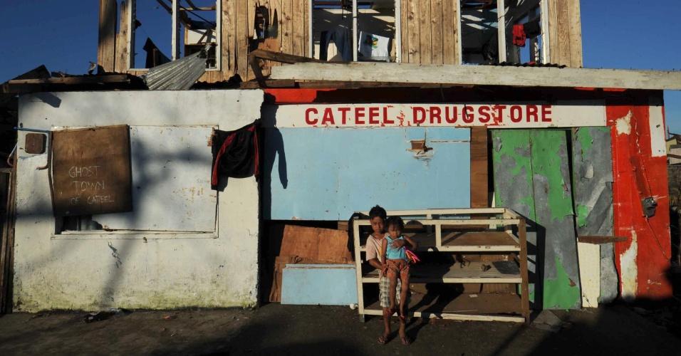 11.dez.2012 - Menino segura irmão menor no colo em frente a loja destruída pela passagem do tufão Bopha pela cidade de Cateel, na província filipina de Davao Oriental