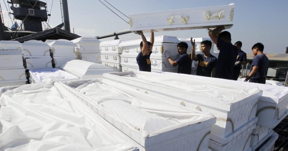 11.dez.2012 - Militares da Marinha filipina carregam caixões que serão doados a famílias carentes que perderam parentes após a passagem do tufão Bopha pelo país