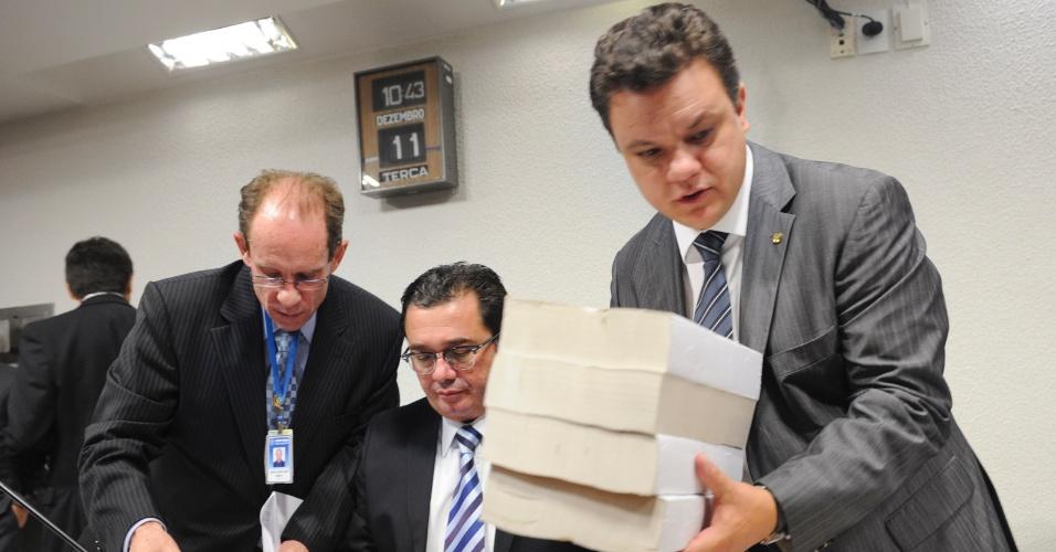 11.dez.2012 - O relator da CPI do Cachoeira, deputado federal Odair Cunha (PT-MG), carrega uma cópia do relatório final da comissão. Nesta terça-feira (11), a votação do relatório foi adiada depois que parlamentares questionaram a manutenção no texto do pedido de indiciamento de jornalistas, o que havia sido previamente acordado para não constar no documento. Cunha justificou que se tratava de um erro de impressão