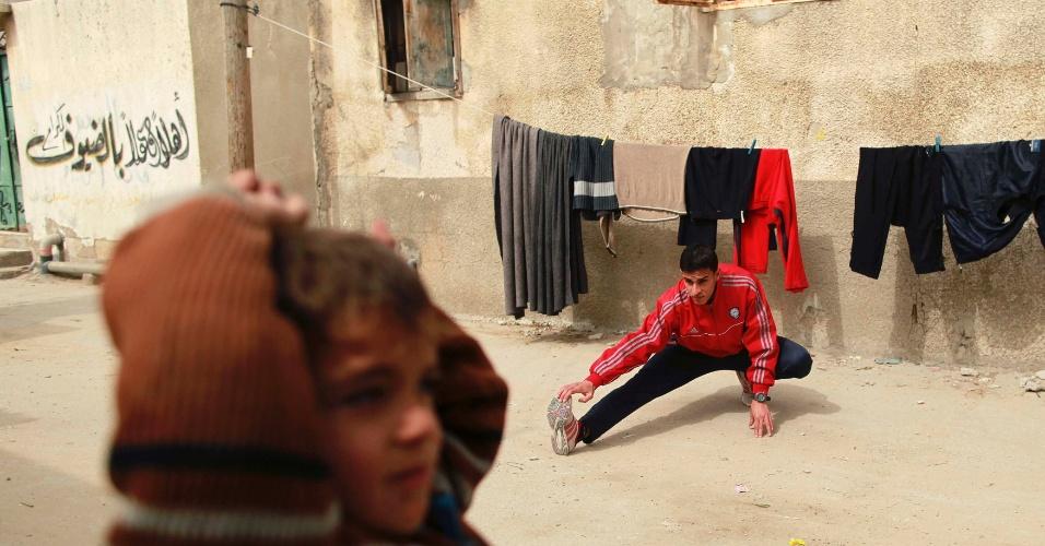 25.mar.2012 - O corredor palestino Bahaa al-Farra, 19, se alonga antes de treinar no campo de refugiados da cidade de Gaza, na faixa de Gaza. Ele participou das Olimpíadas de Londres neste ano