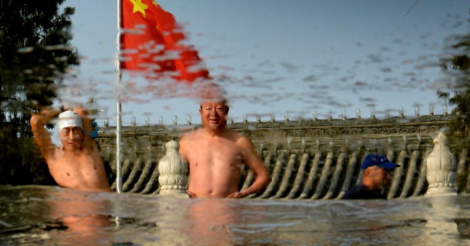 12.dez.2012 - Reflexo de dupla de chineses é visto em lago congelado de Pequim, momentos antes de eles mergulharem na água. A natação no inverno é popular entre idosos e aposentados devido às crenças de que melhora a circulação sanguínea e a atenção, alivia o stress, remove dores, aumenta a vitalidade e rejuvenesce a pele