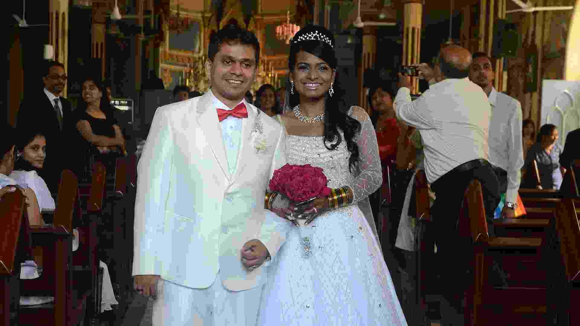 12.dez.2012 - Em templo em Mumbai, na Índia, casal troca o tradicional tapete vermelho por uma faixa com a data 12/12/12 - AFP