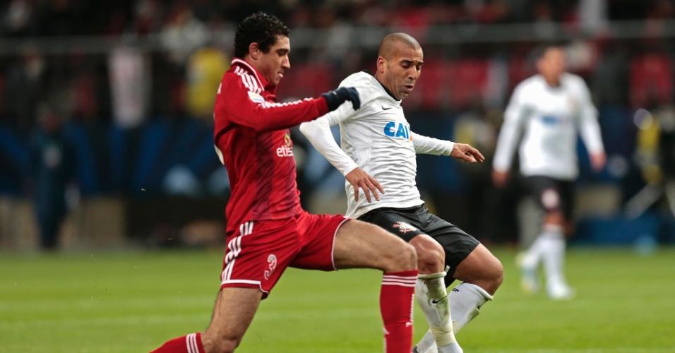 12.dez.2012 - Emerson tenta escapar da marcação de jogador do Al Ahly em lance da vitória corintiana por 1 a 0 na semifinal do Mundial de Clubes