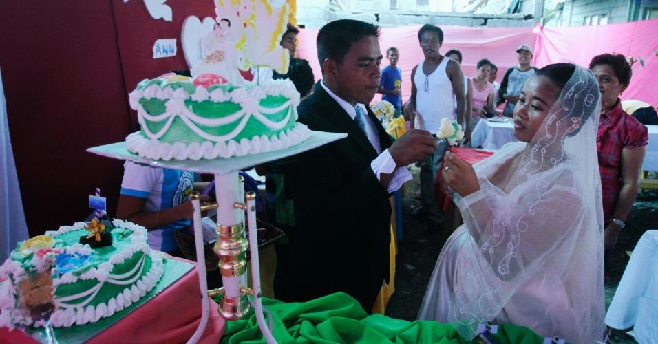 12.dez.2012 - O casal Ronnel Piligrino e Anna Marie Poblacion celebra casamento dentro de abrigo para vítimas do tufão Bopha, em Osmena, nas Filipinas