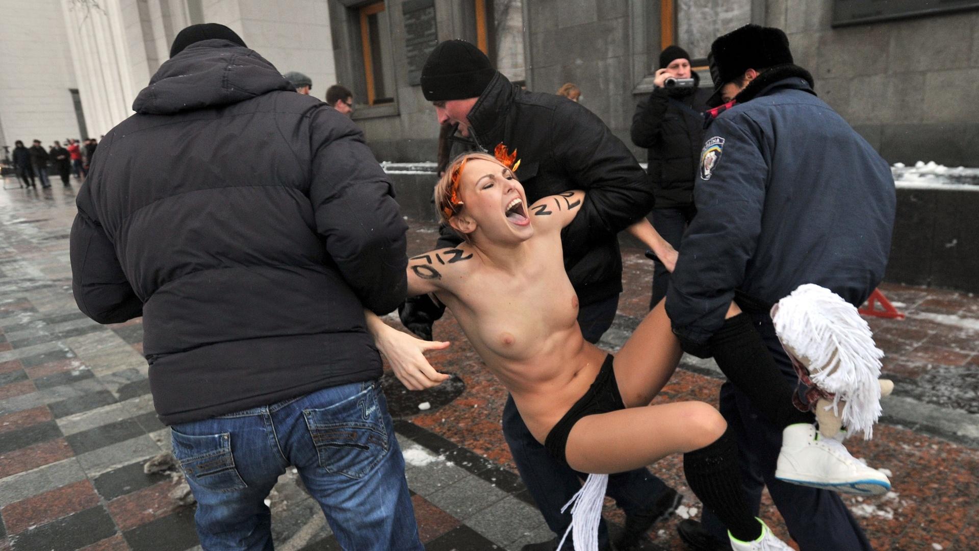 12.dez.2012 - Policiais prendem ativista do grupo feminista Femen durante protesto contra os novos parlamentares ucranianos eleitos, em Kiev, na Ucrânia