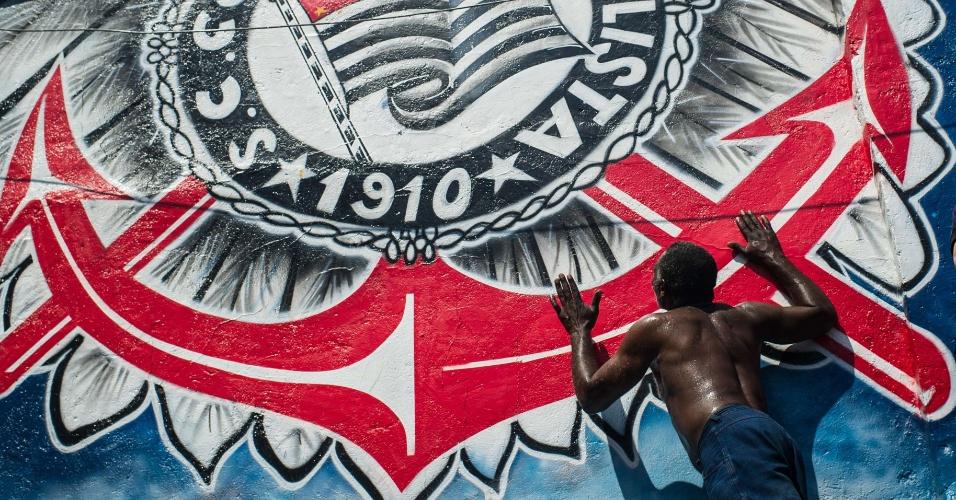 12.dez.2012 - Torcedor corintiano beija escudo gigante do clube em São Paulo