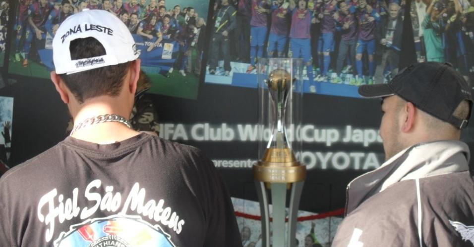 12.dez.2012 - Torcedores do Corinthians observam a taça do Mundial de clubes na entrada do estádio Toyota