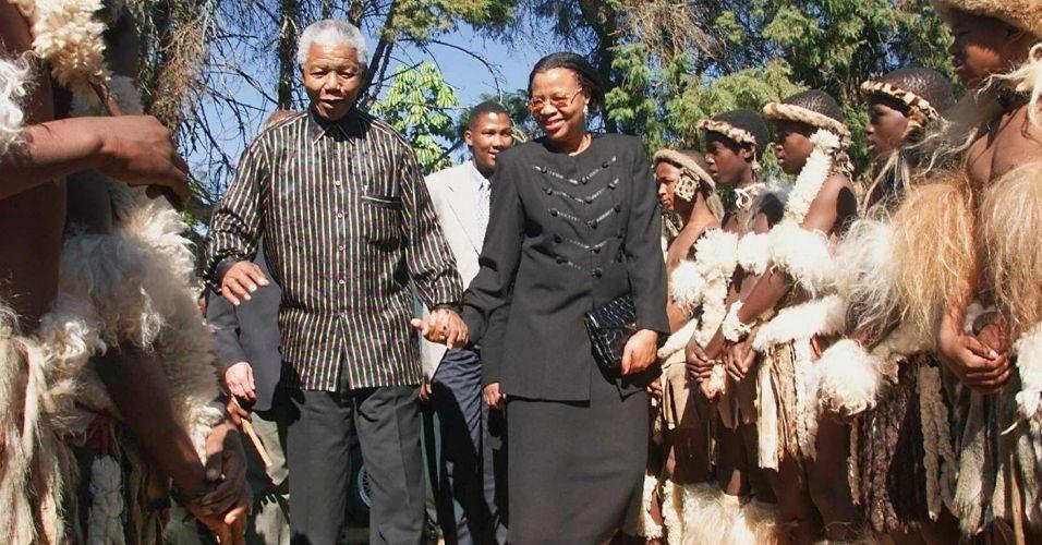 12.jun.1999 - Nelson Mandela e sua mulher, Graça Machel, passam em revista por guarda de honra dos guerreiros Zulus, em Mahhashini