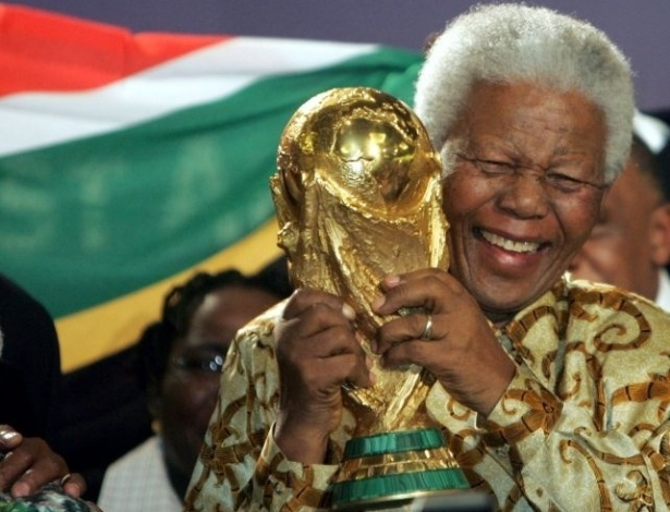 15.mai.2004 - Nelson Mandela segura a Taça Fifa e comemora após ser anunciado que a Copa do Mundo de 2010 seria na África do Sul