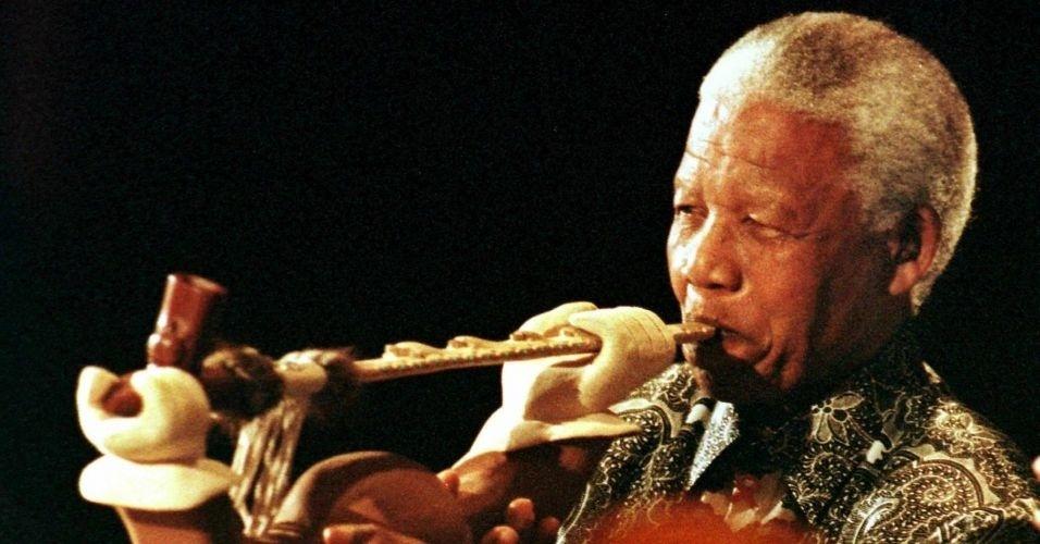 20.nov.2000 - Nelson Mandela fuma um cachimbo típico de nativos americanos, em Minneapolis (EUA)