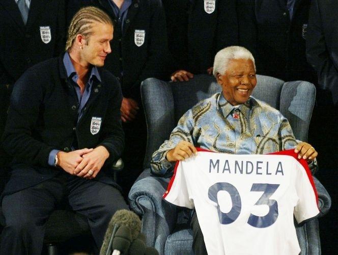 21.mai.2003 - Nelson Mandela recebe camisa de futebol do jogador britânico David Beckham durante visita a Johannesburgo
