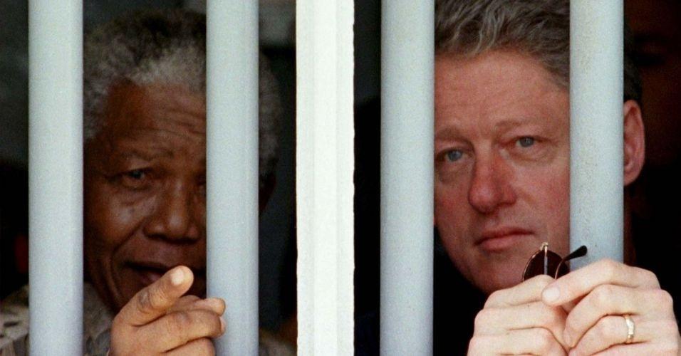 27.mar.1998 - Mandela recebe a visita do então presidente Bill Clinton e leva o norte-americano para conhecer a cela em que ficou preso durante 27 anos