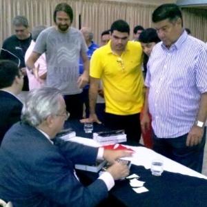 13.dez.2011 Joel Santana (em pé) aguarda assinatura de Eurico Miranda em biografia do ex-presidente do Vasco