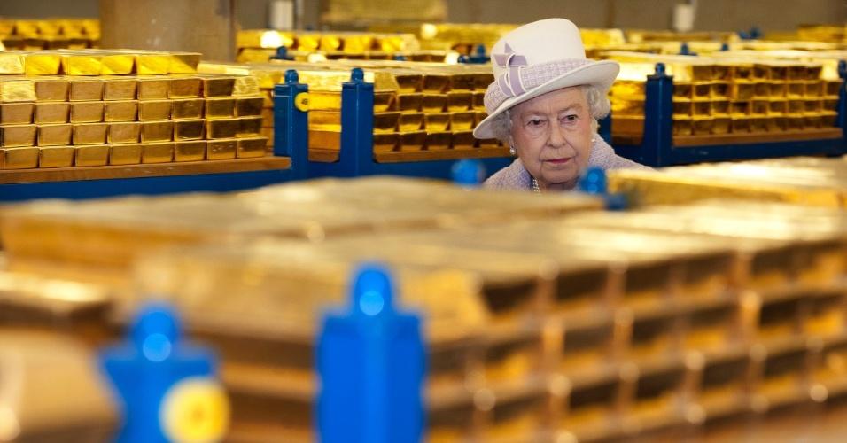 13.dez.2012 - A rainha da Inglaterra, Elizabeth 2ª, anda entre prateleiras com barras de ouro, durante visita ao Banco da Inglaterra, em Londres