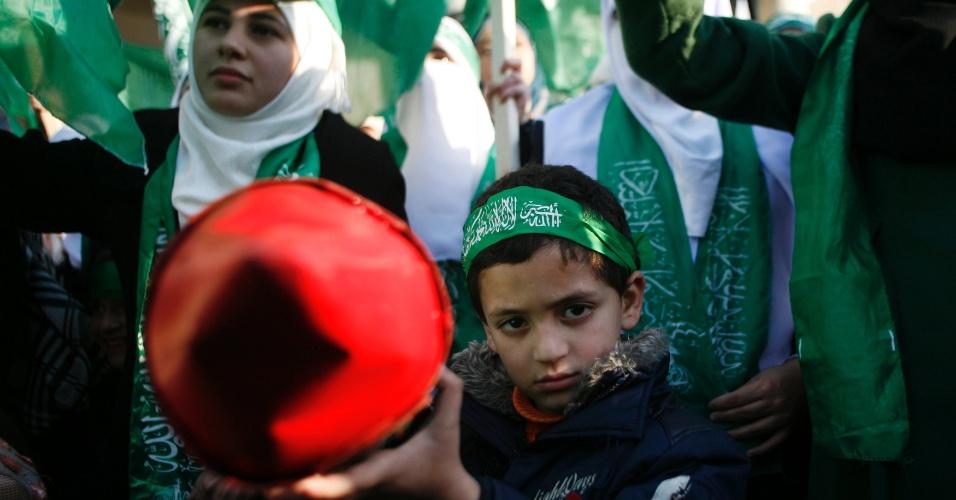 13.dez.2012 - Criança segura modelo de míssil na cidade de Nablus, na Cisjordânia, durante os festejos em comemoração aos 25 anos do grupo islâmico Hamas, comemorado nesta quinta-feira. Esta é a primeira vez desde a divisão entre a Cisjordânia e a Faixa de Gaza em 2007 que a Autoridade Palestina do presidente Mahmud Abbas autoriza o Hamas, no poder em Gaza, para que celebre seu aniversário no território que controla