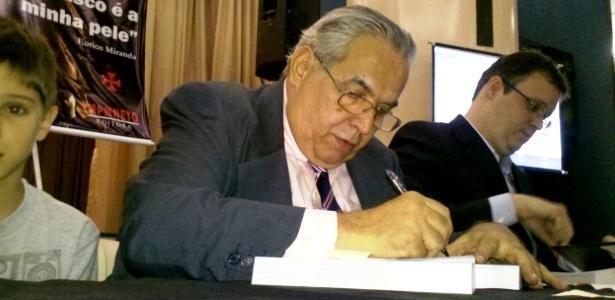 13.dez.2012 Eurico Miranda assina um dos livros durante lançamento de sua biografia