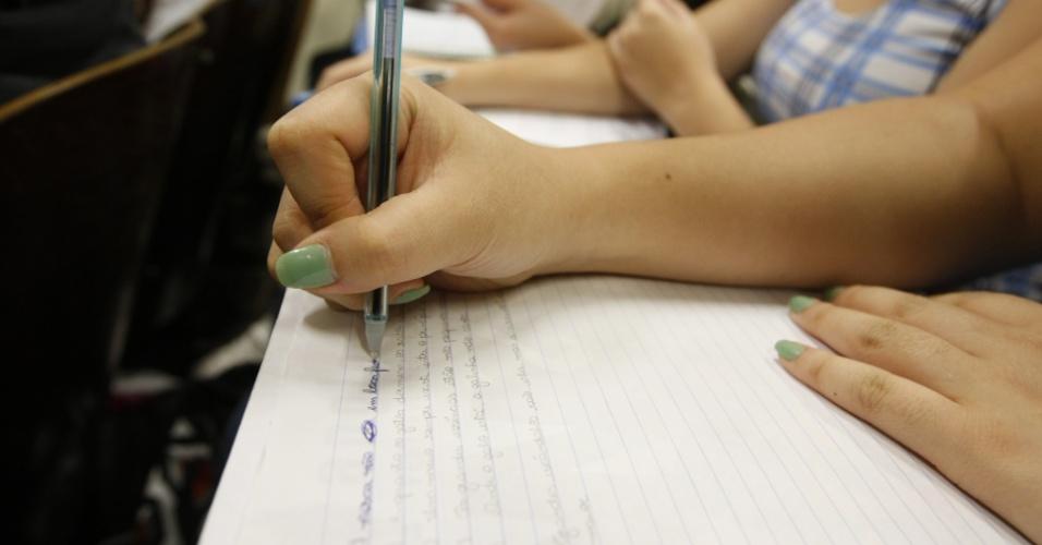 Aluna escreve a caneta sobre rascunho de exercício