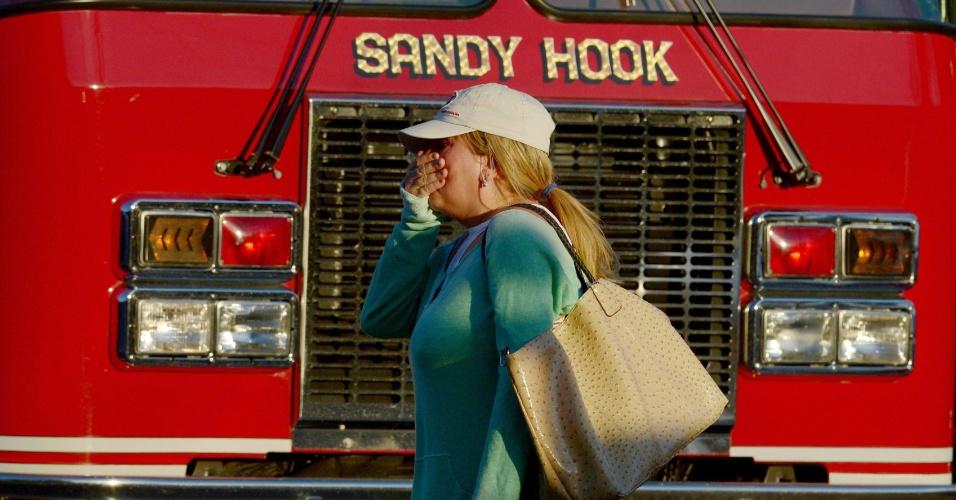 14.dez.2012 - Mulher passa por um caminhão do corpo de bombeiros perto da Escola Primária Sandy Hook, em Connecticut, nos Estados Unidos, após o tiroteio que deixou pelo menos 27 pessoas mortas, incluindo o atirador, o diretor e um psiquiatra da escola, segundo a imprensa local, nesta sexta-feira (14)