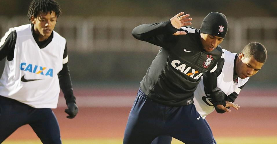 14.dez.2012 - Observado por Romarinho, Paulinho protege a bola durante o treinamento do Corinthians em Yokohama