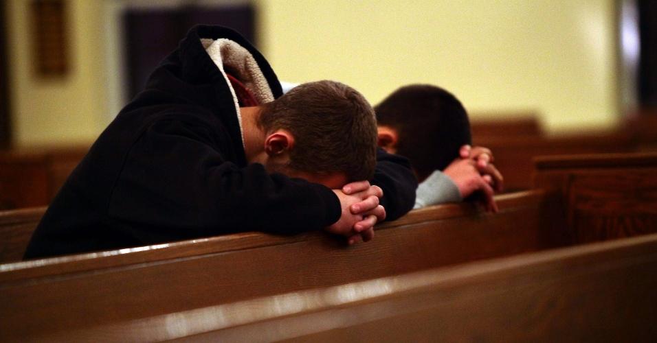 14.dez.2012 - Dois homens oram na igreja St. Rose que fica perto do colégio infantil onde um homem matou 26 pessoas e a si mesmo, em Newtown, Connecticut (EUA). O atirador também é suspeito de matar a própria mãe, em casa