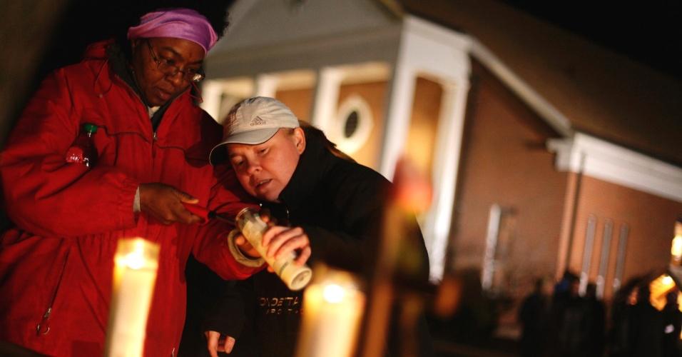 14.dez.2012 - Duas mulheres acendem velas durante uma vigília diante da igreja Saint Rose of Lima, em Newtown, Connecticut, próxima da escola primária Sandy Hook, onde 26 pessoas foram mortas nesta manhã