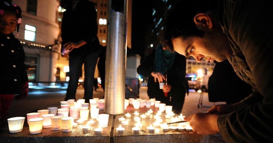 14.dez.2012 - Homem acende uma vela em uma vigília pelas vítimas de Sandy Hook em Oakland, Califórnia, no outro lado dos EUA. Um homem, identificado como Adam Lanza, matou 26 pessoas e a si mesmo, em uma escola primária em Newtown, Connecticut, e é suspeito de matar a mãe, em casa, em um dos piores assassinatos em massa da história dos EUA. O sétimo em 2012