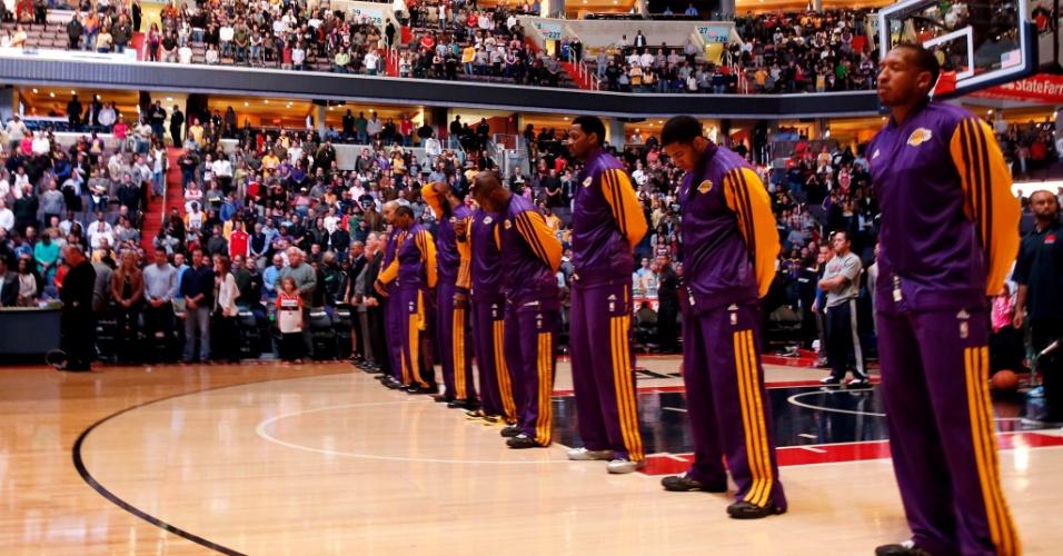 14.dez.2012 - Membros da equipe de basquete Los Angeles Lakers observam um minuto de silêncio em homenagem às vítimas do massacre na escola primária Sandy Hook antes do início do jogo de hoje contra o Washington Wizards, em Washington (Rob Carr/Getty Images/AFP)