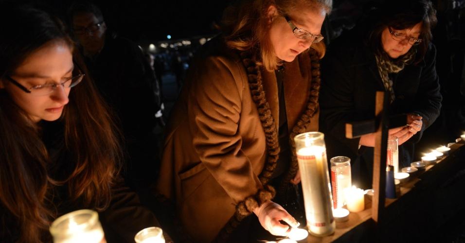 14.dez.2012 - Pessoas se reúnem para uma vigília de oração na igreja St. Rose, em Newtown, Connecticut (EUA). Um homem, identificado como Adam Lanza, matou 26 pessoas e a si mesmo em uma escola primária na cidade. O atirador também é suspeito de matar a própria mãe, em casa