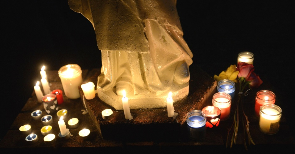 14.dez.2012 - Velas e flores são depositadas em homenagem às vítimas de Sandy Hook, durante vigília diante da igreja Saint Rose of Lima, em Newtown, Connecticut, próxima da escola primária onde 26 pessoas foram mortas nesta manhã