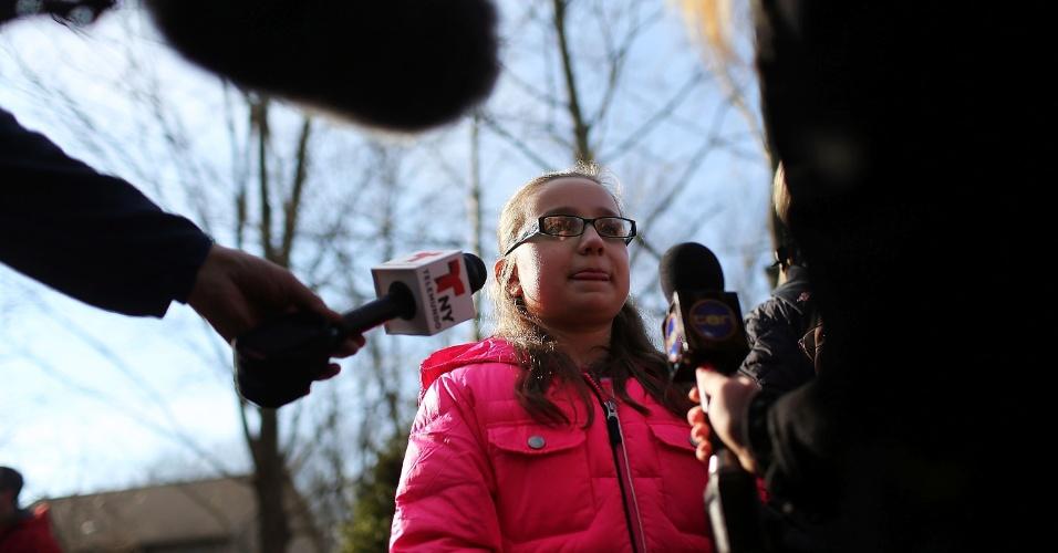 15.dez.2012 - A moradora de Newtown, no Estado de Connecticut (EUA), Molly Villodas, 12, fala com repórteres neste sábado sobre o massacre na escola Sandy Hook, que ocorreu na cidade nesta sexta-feira (14). Um atirador matou 27 pessoas, entre elas 20 crianças, e depois morreu no local. A tragédia chocou os Estados Unidos