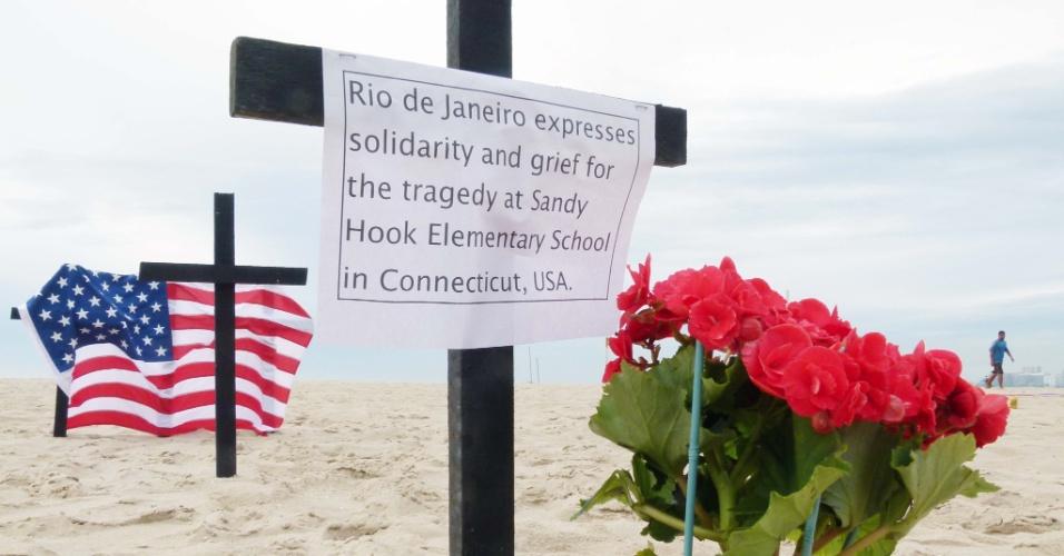 15.dez.2012 - A ONG Rio da Paz faz ato de solidariedade na praia de Copacabana, zona sul do Rio de Janeiro, na manhã deste sábado, às vítimas do massacre em escola primária de Connecticut (EUA). Em inglês, o cartaz diz que o