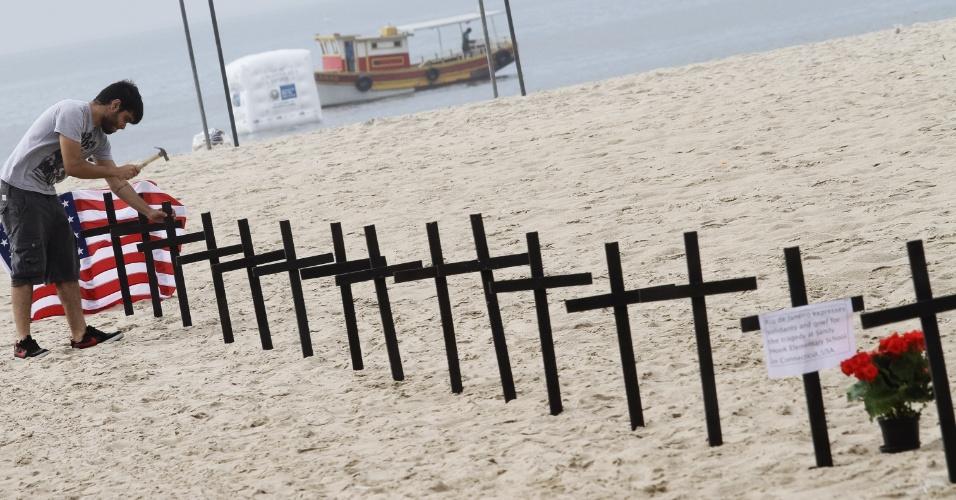 15.dez.2012 - A ONG Rio de Paz faz ato de solidariedade na praia de Copacabana, zona sul do Rio de Janeiro, na manhã deste sábado, às vítimas do massacre em escola primária de Connecticut (EUA). Em inglês, o cartaz diz que o
