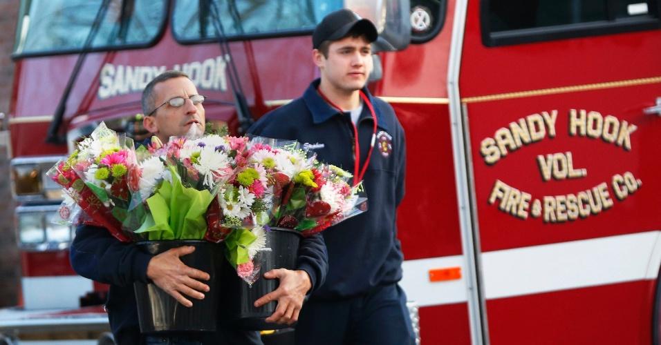 15.dez.2012 - Homem carrega flores enviadas pelos bombeiros para a escola primária Sandy Hook, em Newtown, Connecticut (EUA), em solidariedade às vítimas do massacre ocorrido no local nesta sexta-feira (14). Um atirador matou 27 pessoas, entre elas 20 crianças e depois morreu no local. A tragédia chocou os Estados Unidos