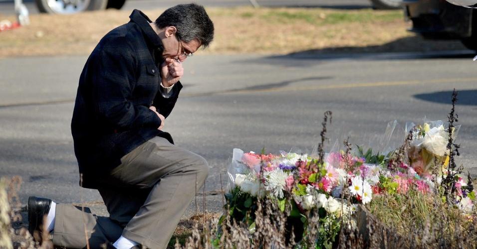15.dez.2012 - Homem faz oração ajoelhado próximo à escola primária Sandy Hook, em Newtown, Connecticut (EUA), neste sábado, onde moradores depositam flores. A escola foi palco de um massacre nesta sexta-feira (14), onde um atirador matou 27 pessoas, entre elas 20 crianças, e morreu em seguida. A tragédia chocou os Estados Unidos