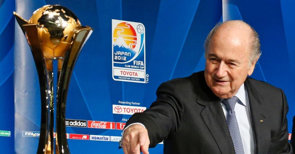 15.dez.2012 - Joseph Blatter, presidente da Fifa, ao lado da taça do Mundial de Clubes, que está sendo disputado no Japão