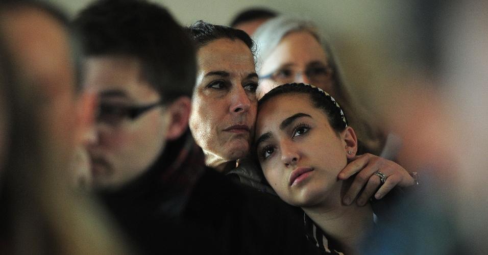 15.dez.2012 - Mãe e filha assistem missa em igreja de Newtown, cidade de Connecticut, neste sábado (15). Na sexta-feira (14), um atirador matou 27 pessoas, entre elas 20 crianças, e depois morreu em escola primária da cidade. A tragédia chocou os Estados Unidos