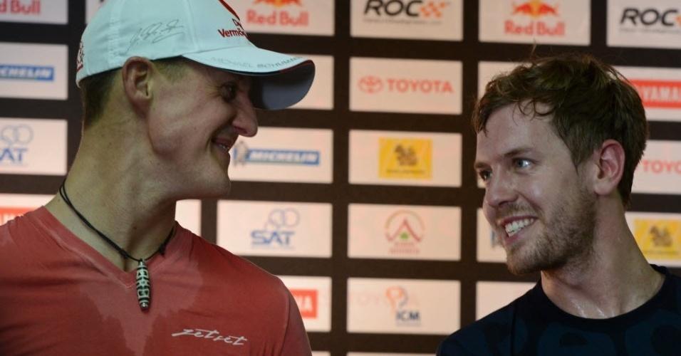 15.dez.2012 - Michael Schumacher (esq.) e Sebastian Vettel conversam durante coletiva de imprensa para a Corrida dos Campeões, competição anual entre nações que reúne os melhores pilotos de várias modalidades do automobilismo e que ocorrerá na Tailândia em 2012