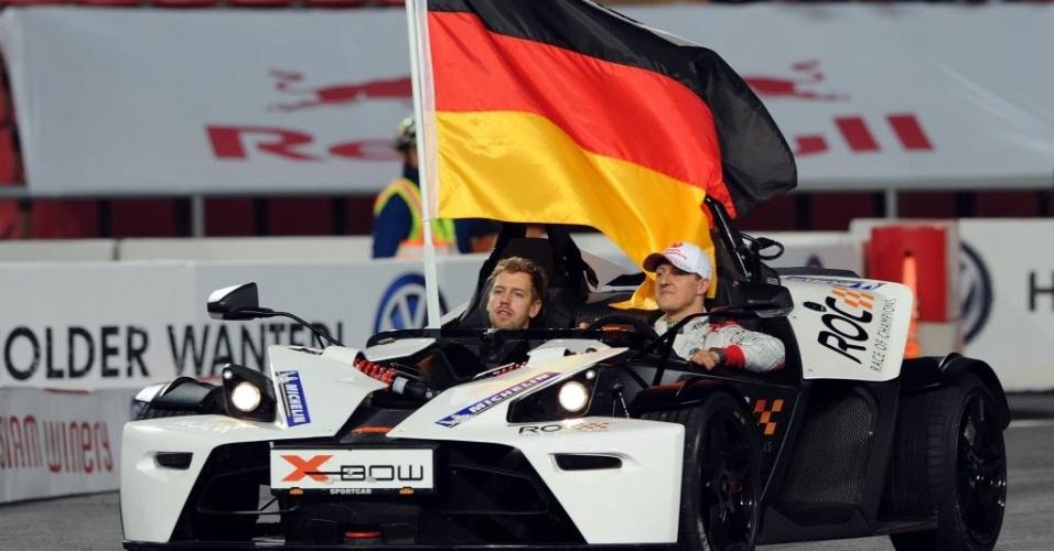 15.dez.2012 - Sebastian Vettel (esq.) e Michael Schumacher se apresentam durante treinamento para a Corrida dos Campeões, competição anual entre nações que reúne os melhores pilotos de várias modalidades do automobilismo e que ocorrerá na Tailândia em 2012