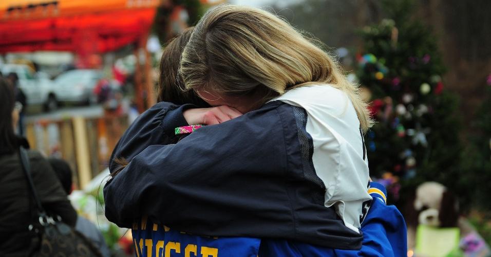 16.dez.2012 - Adolescentes choram em frente ao memorial às vítimas do massacre da escola primária Sandy Hook, decorado com flores, bilhetes e ursos de pelúcia, em Newtown, Connecticut, neste domingo (16). A escola foi palco do massacre de 26 pessoas, entre elas 20 crianças, cometido por um atirador na sexta-feira (14)