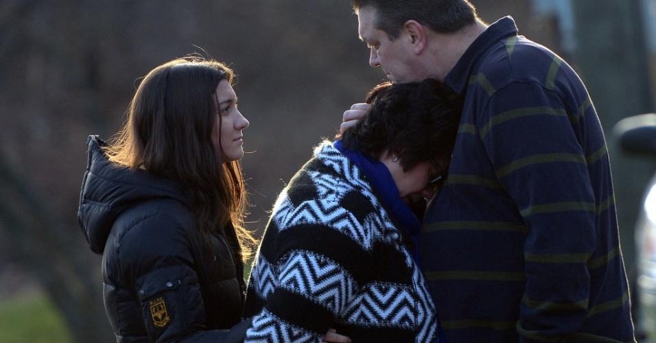 16.dez.2012 - Casal e filha prestam homenagem às vítimas do massacre na cidade de Newtown, no estado norte-americano de Connecticut