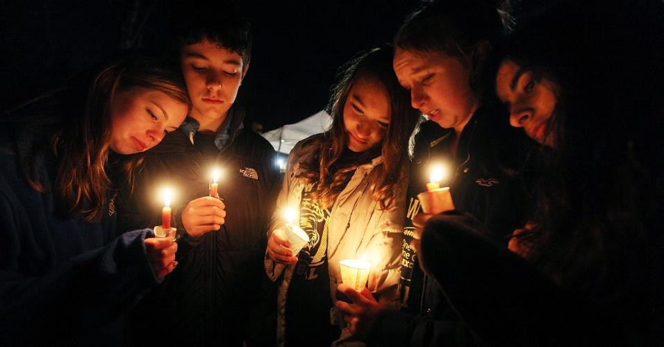 16.dez.2012 - Claire Swanson, Ian Fuchs, Kate Suba, Jaden Albrecht, Simran Chand, moradores de Newtown, Connecticut, seguram velas no memorial das vítimas do massacre da escola primária Sandy Hook, decorado com flores, bilhetes e ursos de pelúcia. A escola foi palco do massacre de 26 pessoas, entre elas 20 crianças, cometido por um atirador na sexta-feira (14)