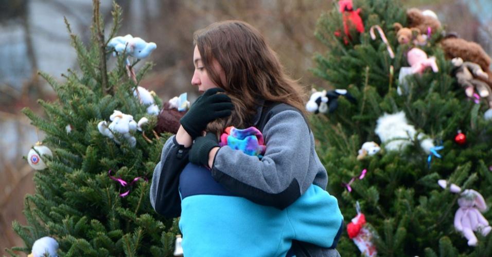 16.dez.2012 - Criança de Newtown, Connecticut (EUA), é consolada em frente ao memorial às vítimas do massacre da escola primária Sandy Hook, decorado com flores, bilhetes e ursos de pelúcia. A escola foi palco do massacre de 26 pessoas, entre elas 20 crianças, realizado por um atirador na sexta-feira (14)