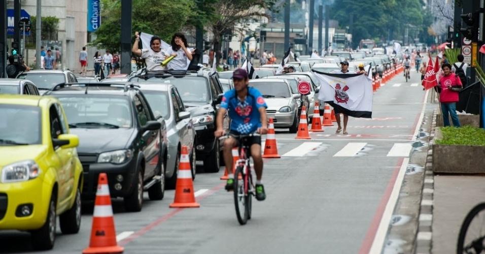16.dez.2012 - Festa de corintianos na Avenida Paulista divide espaço com ciclistas, que passeiam em ciclovia