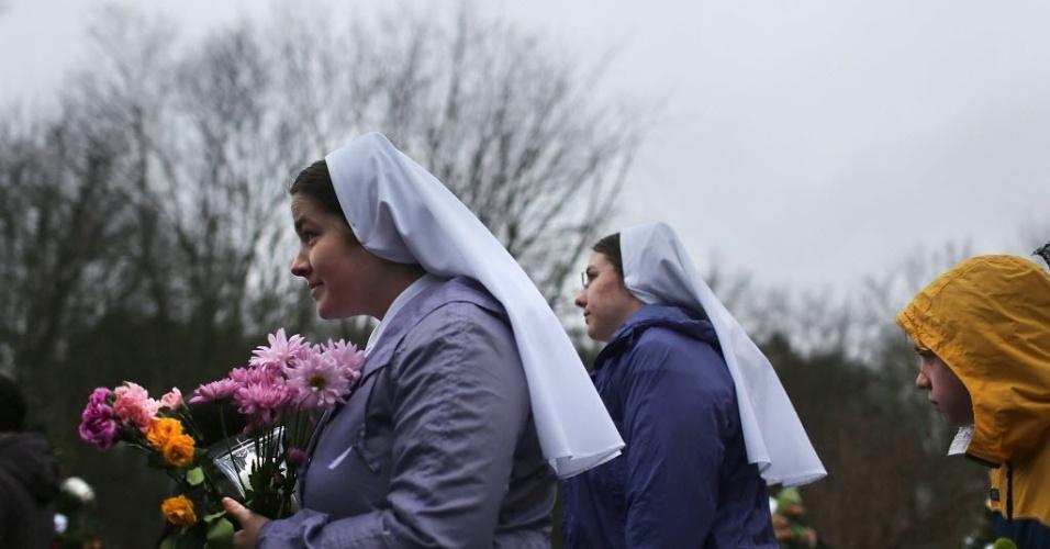16.dez.2012 - Freiras levam flores para depositar na frente da Sandy Hook School, local do assassinato de crianças em Newtown