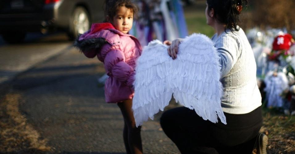 16.dez.2012 - Garota e mulher depositam asas de anjo nas proximidades da Sandy Hook Elementary School, escola que foi cenário de um massacre na última sexta