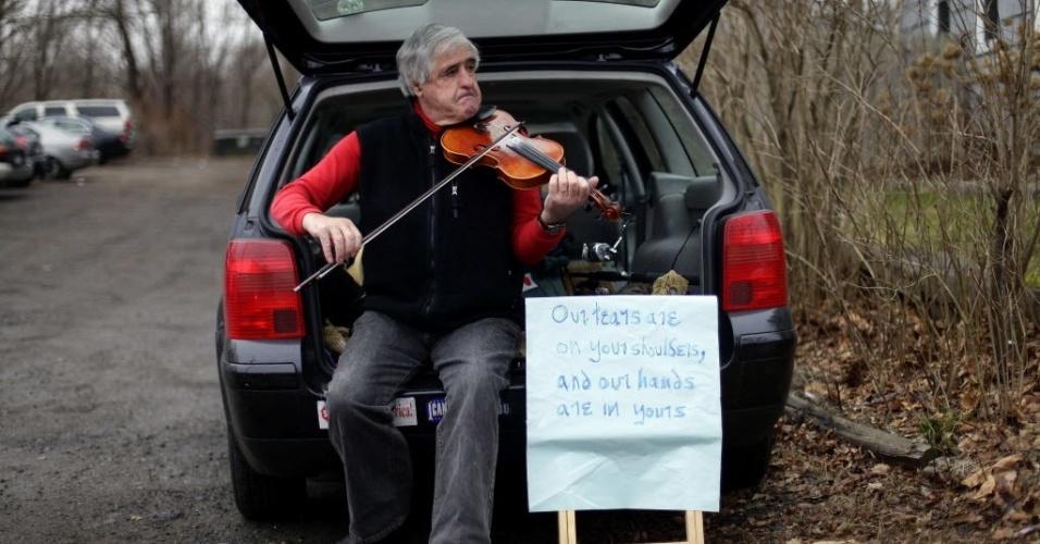 16.dez.2012 - Homem toca violino do lado de fora de igreja em Newtown, cidade onde aconteceu massacre a tiros em escola primária