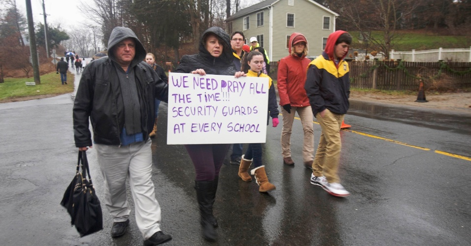 16.dez.2012 - Moradores de Newtown, Connecticut (EUA), caminham pelos arredores da escola primária Sandy Hook fazendo homenagens aos mortos. A escola foi palco do massacre de 26 pessoas, entre elas 20 crianças, cometido por um atirador na sexta-feira (14)
