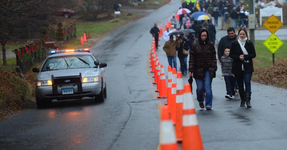 16.dez.2012 - Moradores de Newtown, Connecticut (EUA), são escoltados pela polícia nos arredores da escola primária Sandy Hook. A escola foi palco do massacre de 26 pessoas, entre elas 20 crianças, realizado por um atirador na sexta-feira (14)